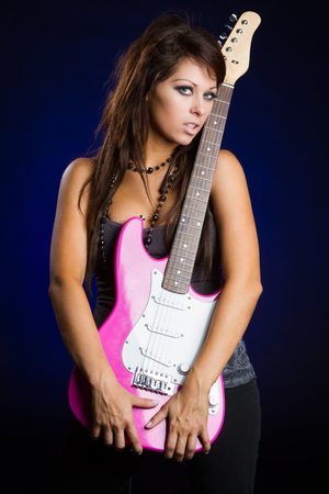 Rocker girl holding pink electric guitar photo