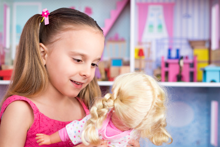 doll house: Pretty little girl playing with doll