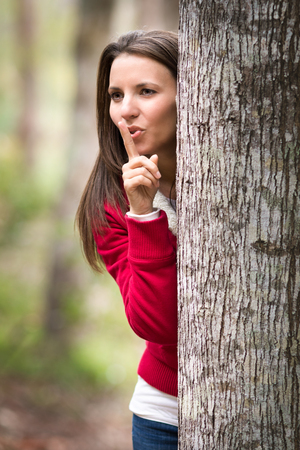 hide and seek: Beautiful woman playing hide and seek behind tree