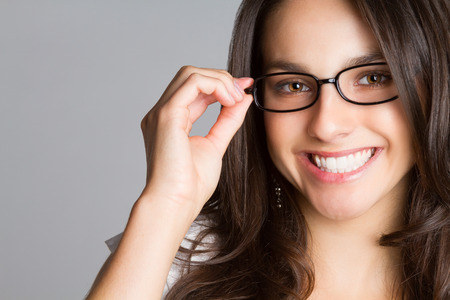 Beautiful young smiling woman wearing glasses photo
