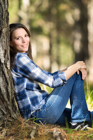 young tree: Beautiful girl sitting by pine tree Stock Photo