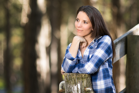 leaning: Beautiful brunette woman leaning on fence Stock Photo