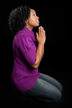 vrouwen: Zwarte vrouw op de knieën bidden Stockfoto