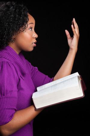 holding bible: Woman worshipping God holding bible Stock Photo
