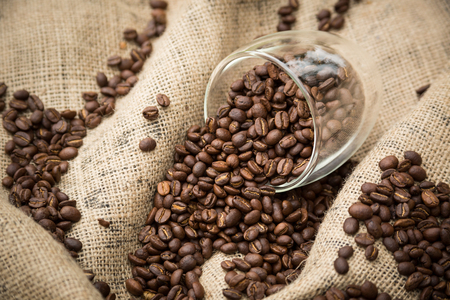 spilling: Coffee beans spilling from glass cup Stock Photo