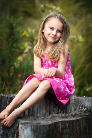 Portrait of little girl sitting on tree stump
