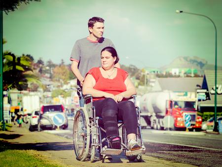 empujando: El hombre empujando a la mujer en silla de ruedas