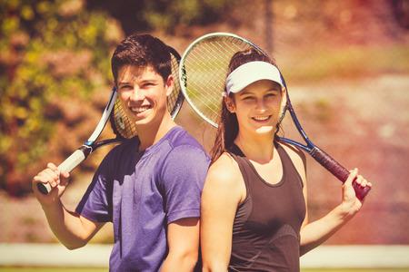 Young boy girl couple playing tennis