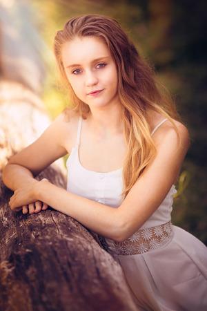blonde yeux bleus: Belle adolescente posant par log
