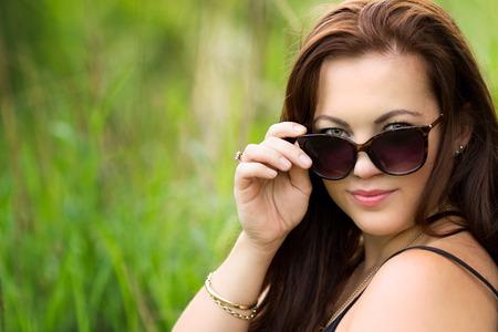 Beautiful woman looking over sunglasses Stock Photo