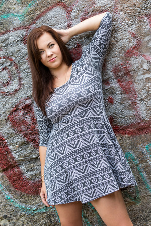 Beautiful woman posing by graffiti wall