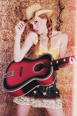 Beautiful redhead woman playing guitar Stock Photo