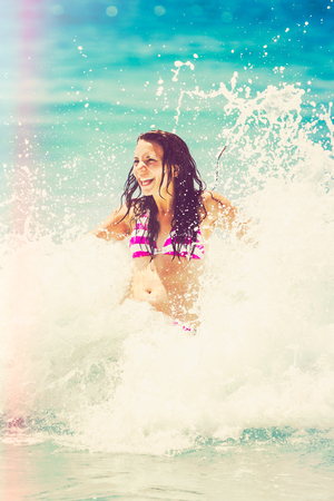 togs: Laughing woman playing in the surf