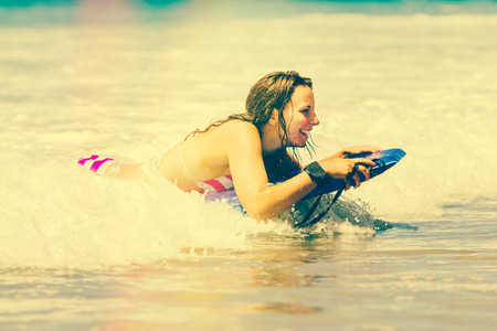 Happy girl boogie boarding at beach