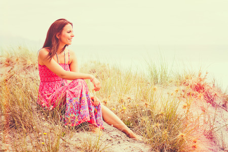 Woman sitting in sand at beach Stock Photo