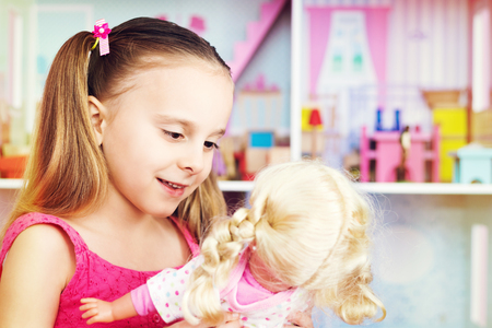 dollhouse: Little girl playing with doll Stock Photo