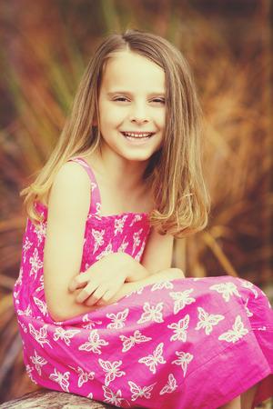 Beautiful little smiling girl portrait sitting Stock Photo