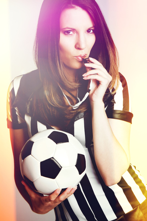 Sexy soccer referee girl blowing whistle photo
