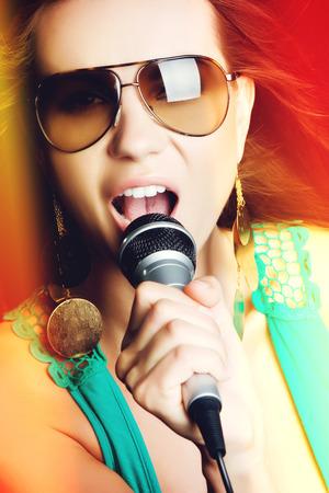 Beautiful popstar woman singing into microphone photo
