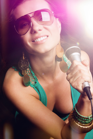 Beautiful pop star girl singing with microphone photo