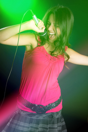 Beautiful karaoke girl singing into microphone photo