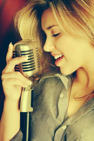 Beautiful woman singing into microphone photo