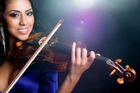 Beautiful smiling latin woman playing violin Stock Photo