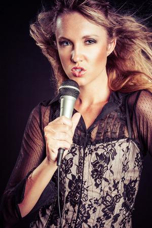 Woman singing karaoke with microphone