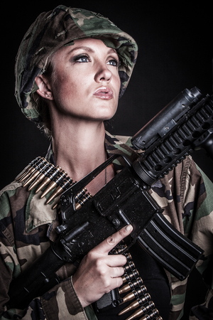 Beautiful female military soldier with gun photo