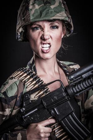 Woman soldier with military machine gun Stock Photo