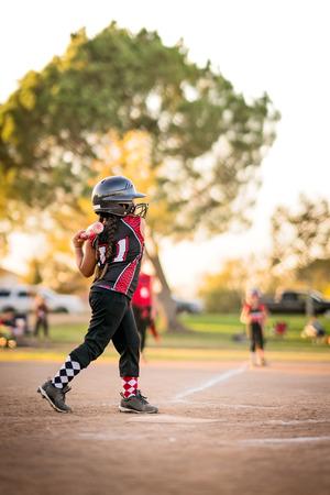 Girl playing little league baseball