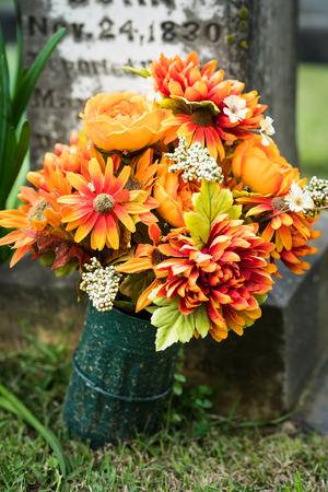 Orange flowers at headstone in graveyard Stock Photo - 100280276