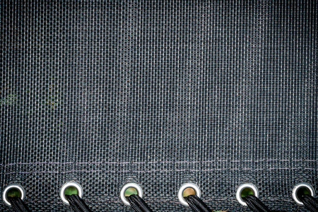 Black fabric background texture with rivets Фото со стока