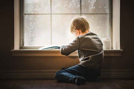Boy reading book by window Stock Photo - 105519477