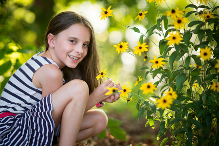 Pretty little girl picking flowers Stock Photo