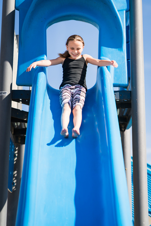 Little girl sliding down playground slide Stock Photo - 104634550