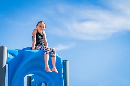Girl sitting on playground equipment Stock Photo