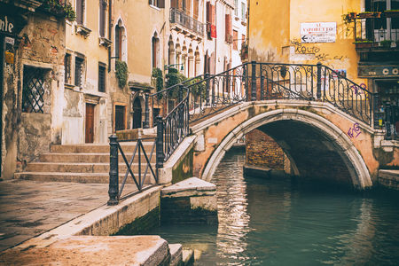 Retro photo of  arched bridge over a narrow canal in Venice, Italy.