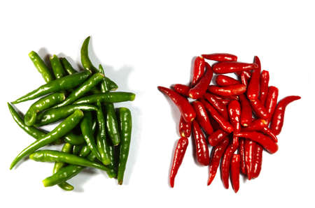 heaps of red and green spicy peppers isolated on white
