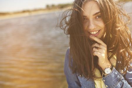 Retrato ensolarado bonito de uma menina tímida olhando para a câmera com o fundo do lago Banco de Imagens