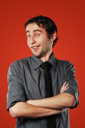 conceited: Expressive comic conceited young man isolated on red background