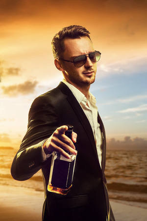 Attractive disheveled young man wearing elegant black suit and sunglasses holding a bottle of whiskey and pointing ahead after party on sunset beach background