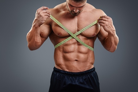 nude abs: Closeup of sports man measuring his waist with a tape measure. Bodybuilder with sexy six packs abs measures gain in waist isolated over gray background.