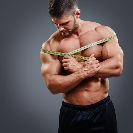 nude male body: Muscular bodybuilder measuring shoulders with tape measure, standing isolated over gray background. Fitness male model shoulder gain concept.