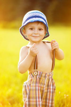 suspender: Portrait of adorable little boy holding his suspender pants