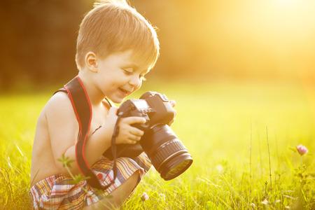 Красивая улыбка ребенок мальчик держит камеру DSLR в парке Фото со стока