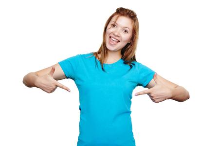 t 셔츠 디자인 개념입니다. 흰색에 고립 된 두 손으로 그녀의 파란 셔츠에 빈 공간을 가리키는 흥분 행복 한 젊은 여자,