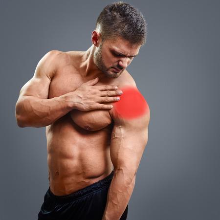 Homem descamisado muscular com dor no ombro sobre o fundo cinzento. Conceito com destaque mancha vermelha brilhante.
