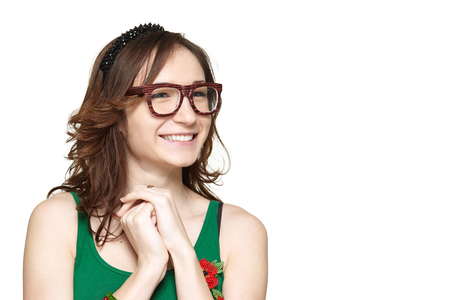 nerd girl: Cute and shy young woman smiling and looking at copy space, isolated on white background. Nerd girl holding hands together
