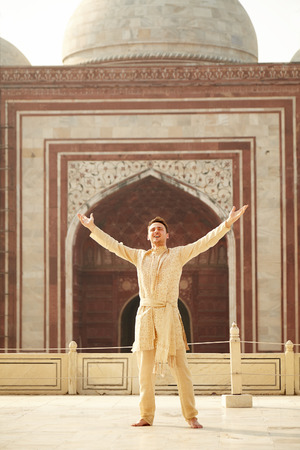 kurta: Smiling Man wearing indian clothes - kurta with open arms standing on Taj Mahal background Stock Photo